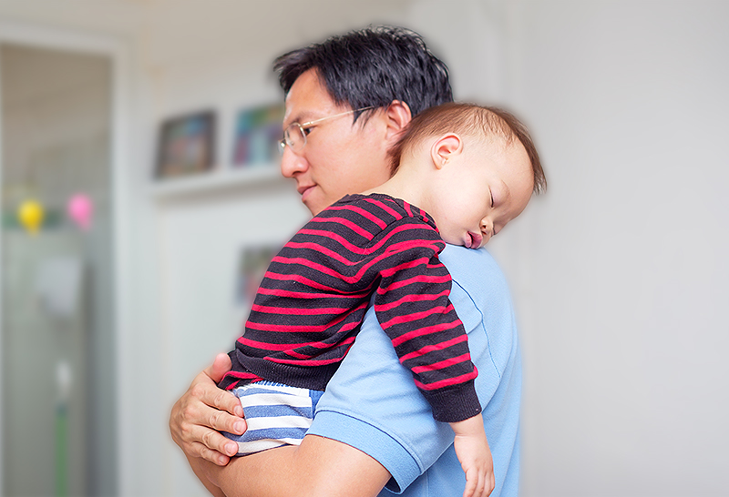 asian father holding sleeping toddler