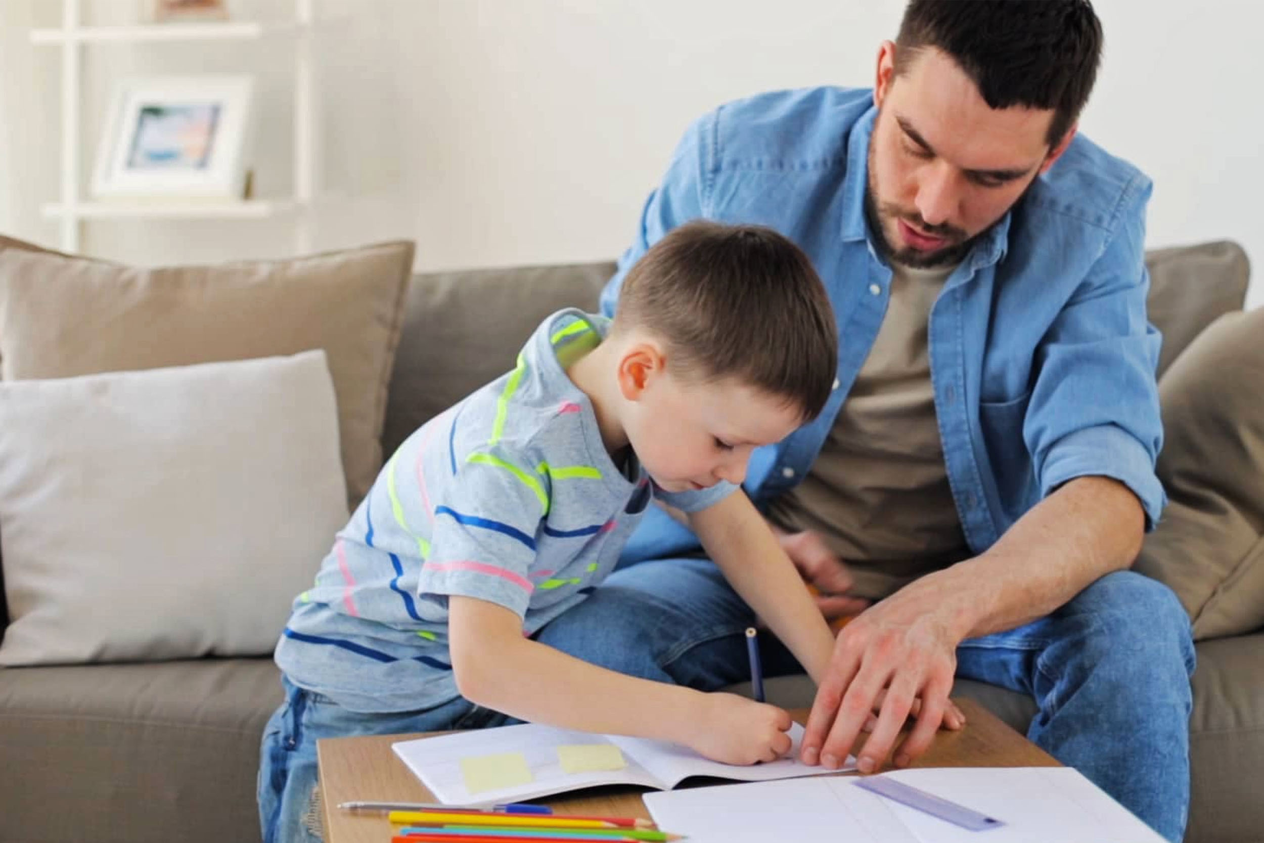 father helping son draw in living room on small table