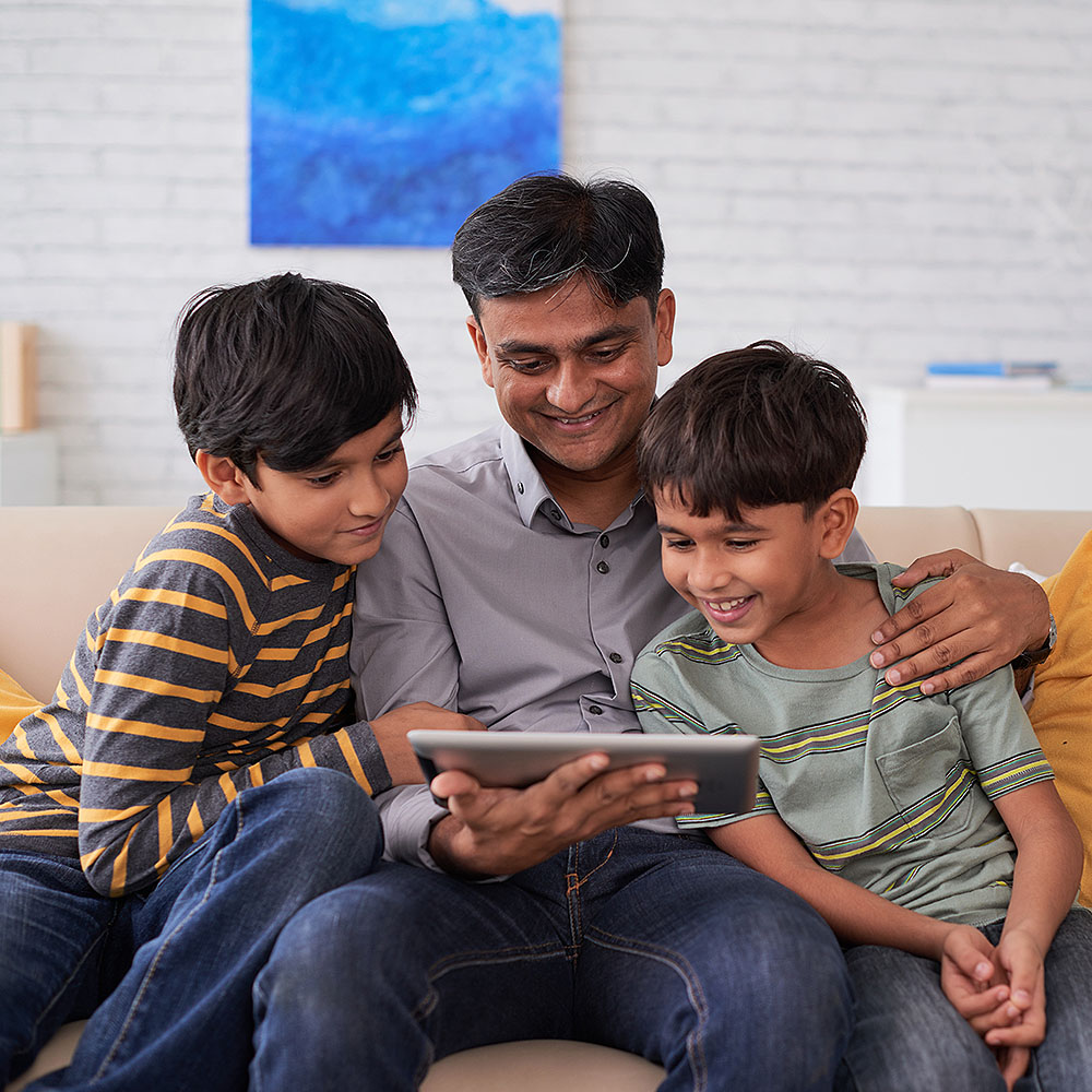 Father looking at a tablet with two young sons